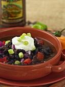 Schwarze Bohnen-Suppe mit Sauerrahm und Zwiebelwürfel