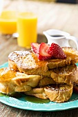 Stack of French Toast with Maply Syrup and Strawberries; Orange Juice