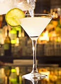 Pouring a Lemon Drop Martini into a Glass from Pitcher; On Bar
