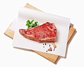 Raw Steak on Parchment with Spices; On Cutting Board