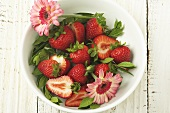 Whole and Sliced Fresh Strawberries in a Bowl; Pink Flowers