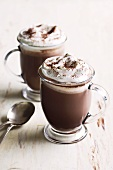Two glass mugs of cocoa with cream