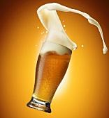 Bierschaum spritzt aus dem Glas