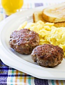 Breakfast Sausage Patties on a Plate with Scrambled Eggs and Toast; Orange Juice