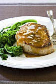 Pork Chop with Sauce and Broccolini on a White Plate