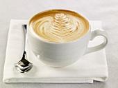 Caffe Latte mit Milchschaum in weisser Tasse auf Serviette