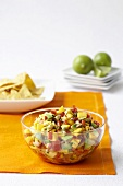 Fresh Mango Salsa in a Glass Bowl; Tortilla Chips; Limes