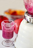 Pomegranate Fruit Smoothie in a Small Glass; Partially Consumed; Blender