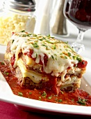 Piece of Lasagna with Tomato Sauce on a White Plate