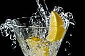 Soda Water Splashing Into a Glass with Lemon Slices