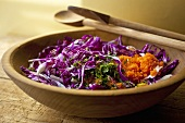 Purple Cabbage Salad in a Wooden Bowl with Wooden Serving Spoons