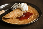 Thin Pancake with Jelly and Whipped Cream; On a Plate; Fork