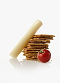 Cheese Stick with a Stack of Crackers and a Tomato