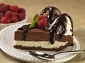 Slice of Layered Ice Cream and Cheese Cake Topped with Two Scoops of Ice Cream and Chocolate Sauce