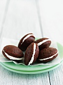 Mini Red Velvet Whoopie Pies on Stacked Green Plates
