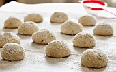 Wedding Cookies Dusted with Powdered Sugar on Parchment Paper