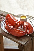 Boiled Lobster with Melted Butter on a Tin Plate; On Wooden Crate
