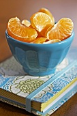 Small Blue Bowl Filled with Clementine Segments on a Decorative Journal