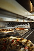 Two Assorted Pizzas Baking in a Pizza Oven