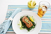 Grilled Salmon over Spinach with Lemon Wedges; Glass of Iced Tea