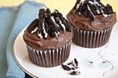 Two Chocolate Frosted Cupcakes Topped with Oreo Cookies
