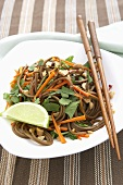 Asian Soba Noodles with Carrots and Peanuts; Chopsticks and Lime Wedge