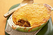 Beef Tamale Casserole with Scoop Removed; In Baking Dish; Wooden Spoon