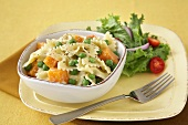 Farfalle Pasta with Peas and Squash in a Bowl; Fork; Side Salad