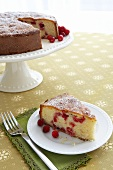 Slice of Cranberry Cornmeal Cake on a Plate; Cake on Cake Stand in Background