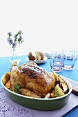 Whole Roast Chicken in Baking Dish with Vegetables; On Table