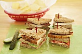 Club Sandwich Wedges with Toothpicks on Cutting Board; Pickles; Basket of Chips