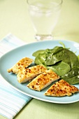 Sliced Seasoned Chicken Breast with Baby Spinach on a Blue Plate