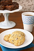 Chocolate Chip Cookies on a Plate; Cup of Coffee; Brownies on Pedestal Dish