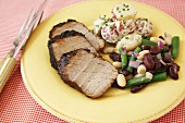 Roast Pork Slices with Bean Salad and Potato Salad on a Plate