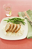 Sliced Pork Tenderloin Over White Rice with Green Beans; Glass of Water with Lime