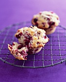 Two cranberry muffins on a wire rack