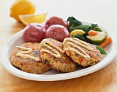Crab Cakes with Red Potatoes and Vegetables on a White Plate