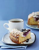 A Piece of Blueberry Coffee Cake with a Cup of Coffee