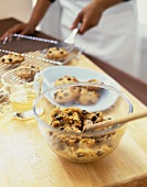 Bowl of Chocolate Chip Cookie Dough; Person Removing Baked Cookies from a Cooling Rack in Background