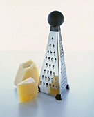 Two Chunks of Parmesan Cheese with a Box Grater