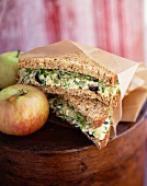 Egg Salad Sandwich with Sprouts on Wheat Bread; Wrapped in Paper with an Apple