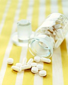 White Pills Spilling From a Bottle; On Yellow and White Striped Background