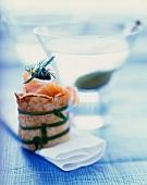Pfannkuchenröllchen mit Räucherlachs vor Martiniglas
