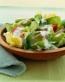 Green Salad in a Wooden Bowl with Creamy Dressing