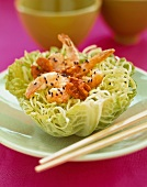 Honey Walnut Shrimp Served in a Cabbage Bowl Garnished with Black Sesame Seeds; Chopsticks