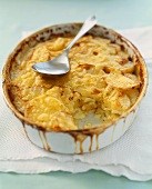 Garlic Potato Gratin in a Baking Dish with a Scoop Removed; Serving Spoon