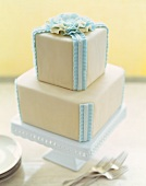 Two Tiered Cake with Blue Frosting Ribbons and Flower; On Cake Plate