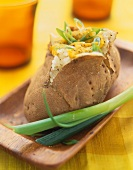 A Baked Potato with Green Onion on a Wooden Dish