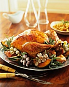 A whole roast turkey with fresh herbs, grapes and pumpkin