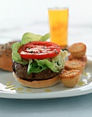 A hamburger with lettuce and tomatoes, roast potatoes and beer